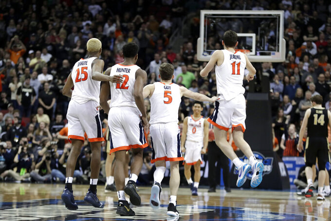 Members of Virginia celebrate during overtime of the men's NCAA Tournament college basketball South Regional final game against Purdue, Saturday, March 30, 2019, in Louisville, Ky. Virginia won 80-75. (AP Photo/Michael Conroy)