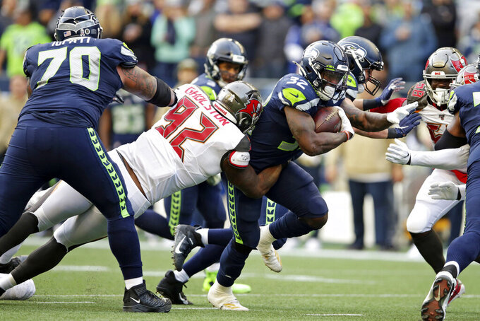 Seattle Seahawks running back Chris Carson (32) is tackled by Tampa Bay Buccaneers defensive tackle William Gholston (92) during the second half of an NFL football game, Sunday, Nov. 3, 2019, in Seattle. (AP Photo/Scott Eklund)