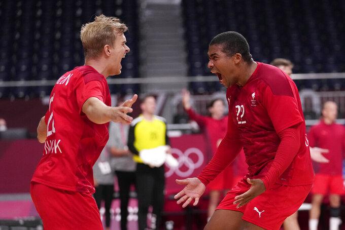 Denmark's Mads Mensah, right, and Johan Hansen celebrate as they won the men's semifinal handball match between Spain and Denmark at the 2020 Summer Olympics, Thursday, Aug. 5, 2021, in Tokyo, Japan. (AP Photo/Pavel Golovkin)