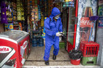 A health worker sprays disinfectant to sanitize a grocery store amid the new coronavirus pandemic in Quetzaltenango, Guatemala, Saturday, Aug. 8, 2020. (AP Photo/Moises Castillo)