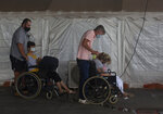 Patients wait to be attended to at the Steve Biko Academic Hospital's outside parking area in Pretoria, South Africa, Monday, Jan. 11, 2021. As the numbers of new confirmed cases rise, South Africa's hospitals are exceeding capacity, according to health officials. (AP Photo/Denis Farrell)