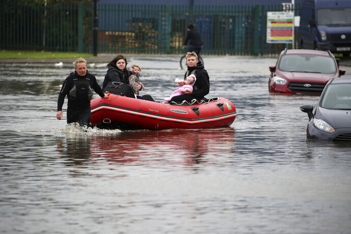 A young man feeds a child a bottle of milk as his father pulls an inflatable boat they have been using to rescue residents trapped by floodwater in Doncaster, northern England, Friday, Nov. 8, 2019. Torrential rain has drenched parts of north and central England, forcing some to evacuate their homes and stranding a small group of people in a shopping center overnight. Floods hit the city of Sheffield, where the River Don overflowed after 3.4 inches (85 mm) of rain fell on Thursday. The Environment Agency says the highest rainfall was registered in Swineshaw, in the Peak District — 4.4 inches (112 mm) in the same period. (Danny Lawson/PA via AP)