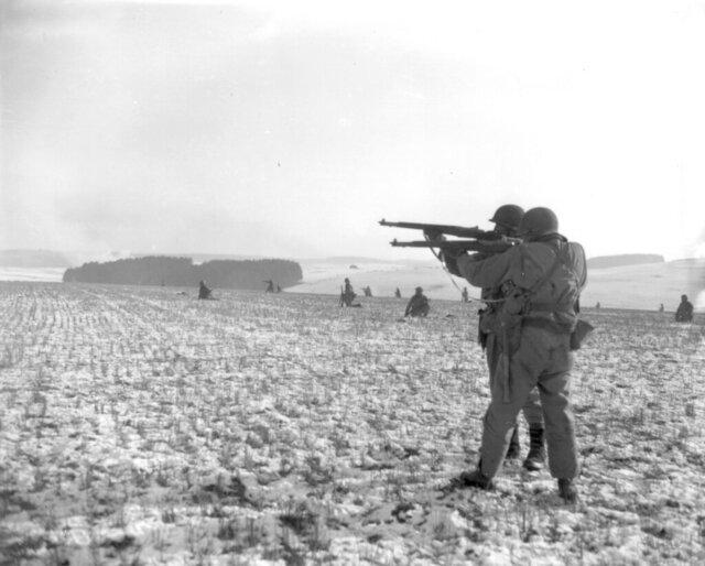 "FILE - In this Dec. 27, 1944, file photo, American infantrymen of the 4th Armored Division fire at German troops, in an advance to relieve pressure on surrounded U.S. airborne units, near Bastogne, Belgium. In 2020, the world marked the 75th anniversary of the end of World War II. Sterling Publishing, in cooperation with The Associated Press, released an illustrated book called ""Victory: World War II In Real Time,"" filled with original AP dispatches from the time to mark the occasion and scores of original news photos. (U.S. Army via AP)"