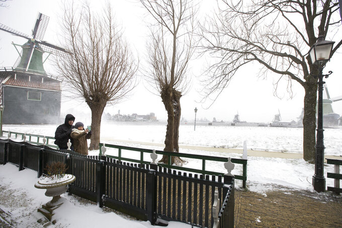 People take a selfie at the Zaans Museum in Zaandam, as snow and strong winds pounded The Netherlands, Sunday, Feb. 7, 2021. (AP Photo/Peter Dejong)