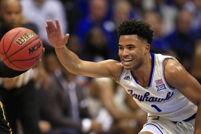 Kansas guard Devon Dotson (1) reaches for a loose ball during the first half of an NCAA college basketball game against Milwaukee in Lawrence, Kan., Tuesday, Dec. 10, 2019. (AP Photo/Orlin Wagner)