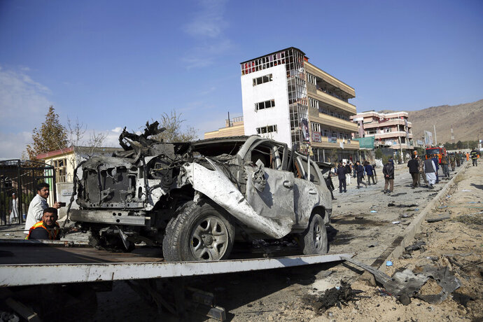 Afghan security personnel remove a damaged vehicle after a car bomb attack in Kabul, Afghanistan, Wednesday, Nov. 13, 2019. A car bomb detonated in the Afghan capital of Kabul during Wednesday's morning commute, killing several people, officials said. (AP Photo/Rahmat Gul)