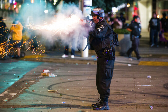 A Los Angeles police officer tries to disperse rowdy fans in the street, Sunday, Oct. 11, 2020, in Los Angeles, after the Los Angeles Lakers defeated the Miami Heat in Game 6 of basketball's NBA Finals to win the championship. (AP Photo/Jintak Han)