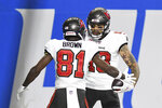 Tampa Bay Buccaneers wide receiver Mike Evans (13) celebrates his 27-yard reception for a touchdown with teammate wide receiver Antonio Brown (81) during the first half of an NFL football game against the Detroit Lions, Saturday, Dec. 26, 2020, in Detroit. (AP Photo/Lon Horwedel)