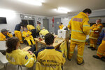 Firefighters standby as nearby fire threatens at the Burragate, Australia, firehouse, Friday, Jan. 10, 2020. Thousands of people are fleeing their homes and helicopters are dropping supplies to towns at risk of wildfires as hot, windy conditions threaten already fire-ravaged southeastern Australian communities. The danger is centered on Australia's most populous states, including coastal towns that lost homes in earlier fires. (AP Photo/Rick Rycroft)