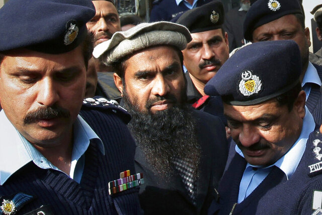 FILE - In this Thursday, Jan. 1, 2015, file photo, Pakistani police officers escort Zaki-ur-Rehman Lakhvi, center, the main suspect of the Mumbai terror attacks in 2008, after his court appearance in Islamabad, Pakistan. Pakistan's security forces arrested Saturday, Jan. 2, 2021 an alleged leader of the militant group that was behind the bloody 2008 Mumbai attacks in India. (AP Photo/B.K. Bangash, File)