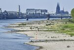 FILE - In this Monday, April 27, 2020 file photo, dry river banks of Germany's most important river, the Rhine, lie exposed in front of the Cologne Cathedral in Cologne, Germany. This April was one of the driest months since records began and creates problems not only for farmers but also for industry. (AP Photo/Martin Meissner)