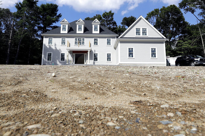 In this Sept. 3, 2019 photo a newly constructed home rests on a plot of land, in Westwood, Mass. On Wednesday, Sept. 25, the Commerce Department reports on sales of new homes in August. (AP Photo/Steven Senne)