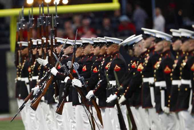The U.S. Marine Corps Silent Drill Platoon, based at Marine barracks, Washington D.C., perform during halftime of an NFL football game between the Atlanta Falcons and the Tampa Bay Buccaneers, Sunday, Nov. 24, 2019, in Atlanta. (AP Photo/John Bazemore)