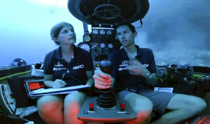 An image taken from video issued by Nekton shows Lucy Woodall, Nekton Mission principle scientist, left, alongside pilot Randy Holt inside a submersible 60 metres below surface of Indian Ocean during a descent into the Indian Ocean off Alphonse Atoll near the Seychelles, Tuesday March 12, 2019. Members of the British-led Nekton research team boarded two submersible vessels and descended into the waters off the Seychelles on Tuesday, marking a defining moment in their mission to document changes to the Indian Ocean. The submersibles will be battling strong undersea currents and potentially challenging weather conditions as they survey the side of an undersea mountain off Alphonse Atoll. (Nekton via AP)