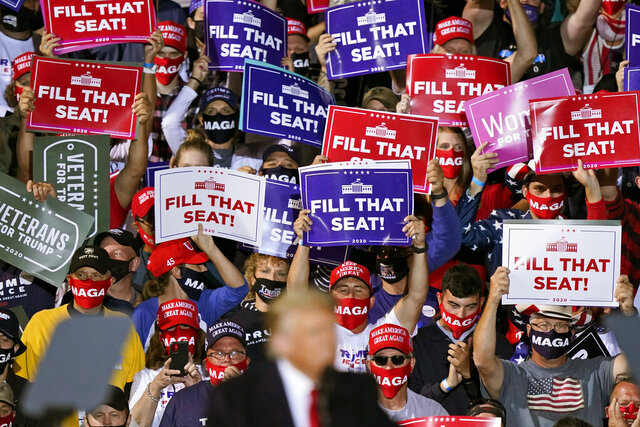 Supporters of President Donald Trump hold up signs as he speaks at a campaign rally, Monday, Sept. 21, 2020, in Swanton, Ohio. (AP Photo/Tony Dejak)