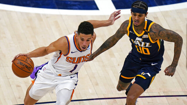 Phoenix Suns guard Devin Booker (1) drives around Utah Jazz guard Jordan Clarkson (00) during the second half of an NBA basketball game Thursday, Dec. 31, 2020, in Salt Lake City. (AP Photo/Rick Bowmer)