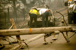 FILE - In this Nov. 10, 2018, file photo, with a downed power utility pole in the foreground, Eric England, right, searches through a friend's vehicle after the wildfire burned through Paradise, Calif. Pacific Gas & Electric's key lenders have offered a $30 billion plan to pull the utility out of bankruptcy, and give the tarnished company a new name. The Sacramento Bee reports the proposal filed Tuesday, June 25, 2019 in U.S. Bankruptcy Court would set aside up to $18 billion to pay claims on the 2017 and 2018 wildfires caused by PG&E equipment.  (AP Photo/Noah Berger, File)