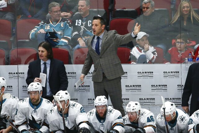 San Jose Sharks interim head coach Bob Boughner, middle, stands on the bench to wave his goalie off the ice as assistant coach Mike Ricci, back left, looks at the action on the ice during the third period of an NHL hockey game against the Arizona Coyotes Tuesday, Jan. 14, 2020, in Glendale, Ariz. The Coyotes defeated the Sharks 6-3. (AP Photo/Ross D. Franklin)
