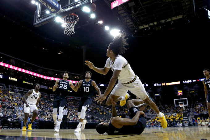Missouri guard Dru Smith, front top right, dives over Butler guard Aaron Thompson, front bottom right, after shooting during the first half of an NCAA college basketball game Monday, Nov. 25, 2019, in Kansas City, Mo. (AP Photo/Charlie Riedel)