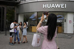 Shoppers stand outside a Huawei store in Beijing on Wednesday, June 2, 2021. Huawei is launching its own HarmonyOS mobile operating system on its handsets as it adapts to losing access to Google mobile services two years ago after the U.S. put the Chinese telecommunications company on a trade blacklist. (AP Photo/Ng Han Guan)