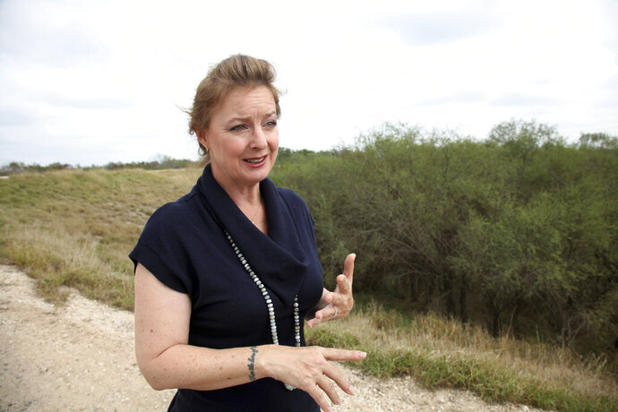 FILE - In this Jan. 8, 2019 file photo, Marianna Trevino-Wright, Executive Director of the National Butterfly Center, talks during an interview with The Associated Press in Mission, Texas. The U.S. government is preparing to begin construction of more border walls and fencing in South Texas' Rio Grande Valley, likely on federally-owned land set aside as wildlife refuge property. Heavy construction equipment is supposed to arrive starting Monday. A photo posted by the nonprofit National Butterfly Center shows an excavator parked on its property.(AP Photo/ John L. Mone)