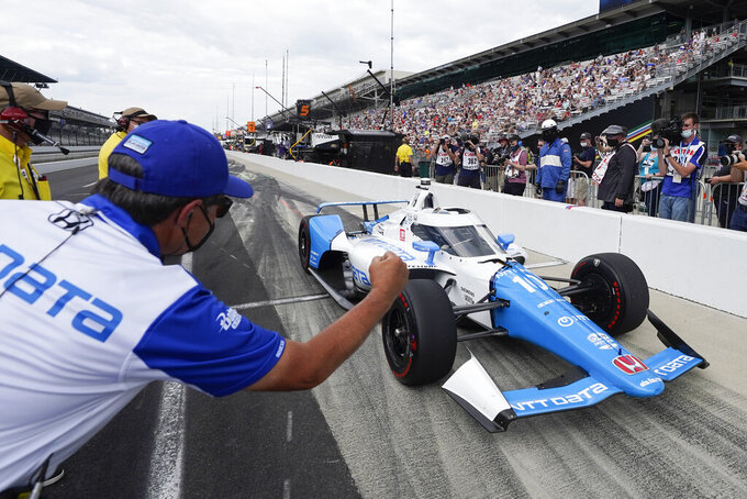 A crew member greets Alex Palou, of Spain, as he pulls in during qualifications for the Indianapolis 500 auto race at Indianapolis Motor Speedway, Sunday, May 23, 2021, in Indianapolis. (AP Photo/Darron Cummings)