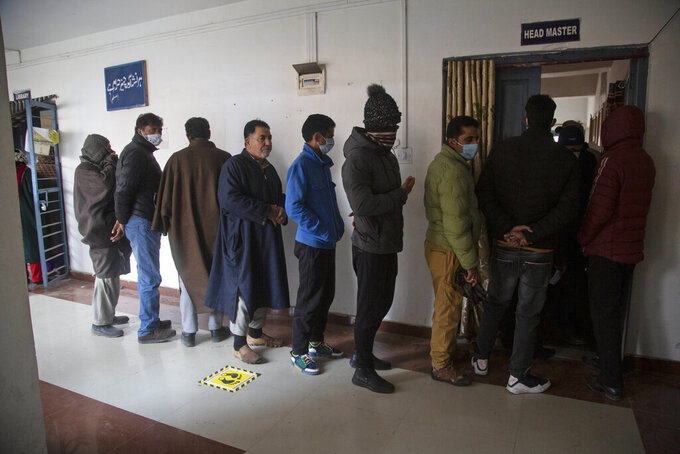 Kashmiris stand in a queue to cast their votes during the first phase of District Development Councils election on the outskirts of Srinagar, Indian controlled Kashmir, Saturday, Nov. 28, 2020. Thousands of people in Indian-controlled Kashmir voted Saturday amid tight security and freezing cold temperatures in the first phase of local elections, the first since New Delhi revoked the disputed region's semiautonomous status. (AP Photo/Mukhtar Khan)