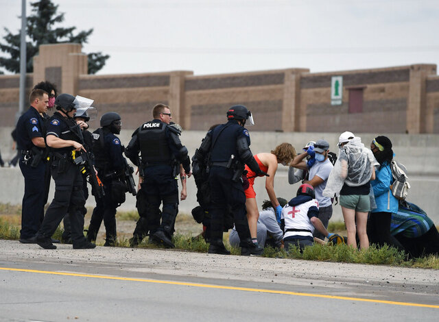 CORRECTS TO POLICE BELIEVE WAS SHOT BY A FELLOW PROTESTER-Aurora Police officers and protest medics attend to an injured demonstrator who police believe was shot by a fellow protester while on Interstate 225, Saturday, July 25, 2020, in Aurora, Colo., during a protest against racial injustice and the death of Elijah McClain, who was stopped by police while walking down an Aurora street in August 2019 after a 911 caller reported him as suspicious. (Andy Cross/The Denver Post via AP)