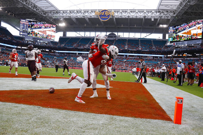 Miami tight end Larry Hodges, foreground, celebrates with running back Cam'Ron Harris after scoring during the second half of an NCAA college football game against Bethune-Cookman, Saturday, Sept. 14, 2019, in Miami Gardens, Fla. (AP Photo/Wilfredo Lee)