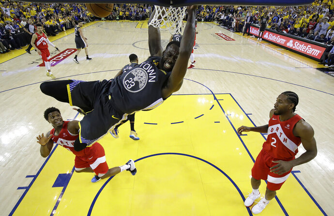 File-This June 13, 2019, file photo shows Golden State Warriors forward Draymond Green (23) dunking over Toronto Raptors guard Kyle Lowry, left, and forward Kawhi Leonard (2) during the first half of Game 6 of basketball's NBA Finals in Oakland, Calif. A person familiar with the situation says the Warriors and Green have agreed on a four-year extension worth nearly $100 million, meaning the three-time All-Star is under contract through the 2023-24 season. Green and the Warriors intend to make the deal official imminently, according to the person who spoke to The Associated Press on condition of anonymity Saturday because it has not been finalized.  (AP Photo/Tony Avelar, Pool, File)