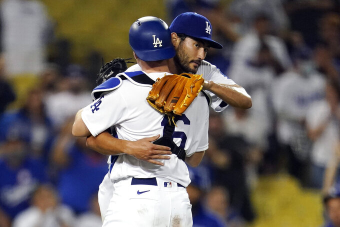 Los Angeles Dodgers relief pitcher Mitch White, right, hugs catcher Will Smith after the team's 9-0 win over the Pittsburgh Pirates in a baseball game Wednesday, Aug. 18, 2021, in Los Angeles. (AP Photo/Marcio Jose Sanchez)