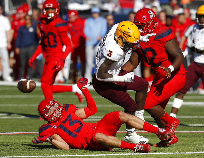 Arizona safety Chacho Ulloa (13) strips the ball from Arizona State running back Eno Benjamin (3) in the first half during an NCAA college football game, Saturday, Nov. 24, 2018, in Tucson, Ariz. (AP Photo/Rick Scuteri)