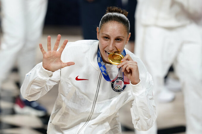 United States's Diana Taurasi bites her gold medal during the medal ceremony for women's basketball at the 2020 Summer Olympics, Sunday, Aug. 8, 2021, in Saitama, Japan. (AP Photo/Charlie Neibergall)
