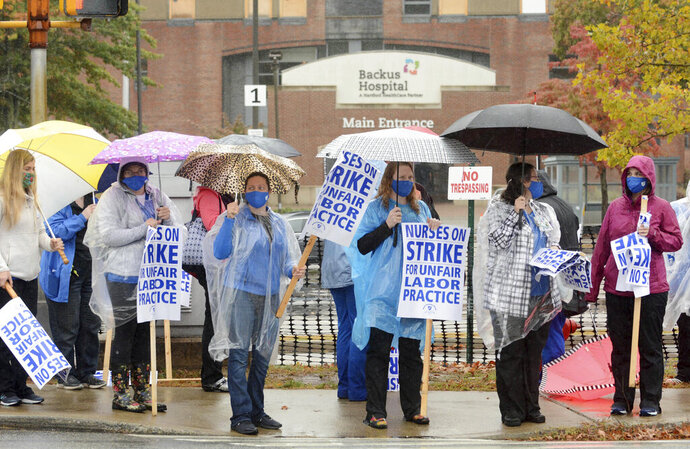 FILE- In this Oct. 13, 2020, file photo, nurses and their supporters hold signs in the rain as they began a two-day strike outside the William W. Backus Hospital in Norwich, Conn. On Wednesday, Oct. 21, 2020, registered nurses at the hospital approved a new, four-year collective bargaining contract after going on a two-day strike amid disputes over pay and the availability of protective gear during the coronavirus pandemic. (John Shishmanian/The Bulletin via AP, File)
