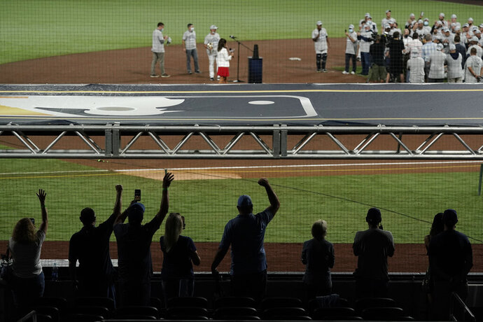 Tampa Bay Rays families celebrate from a distance following the team's victory against the Houston Astros in Game 7 of a baseball American League Championship Series, Saturday, Oct. 17, 2020, in San Diego. The Rays defeated the Astros 4-2 to win the series 4-3 games. (AP Photo/Gregory Bull)