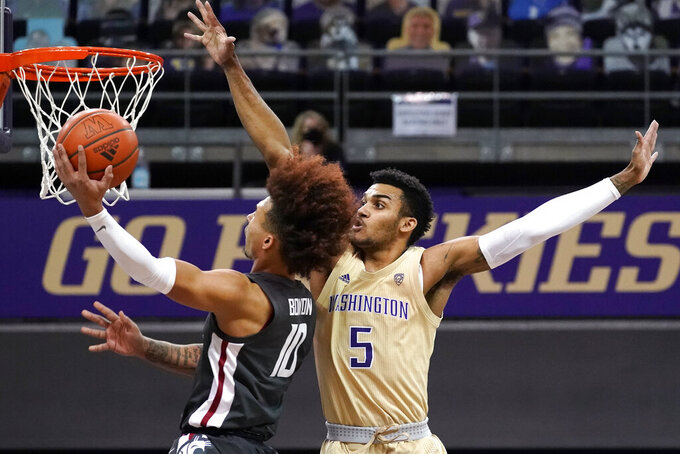 Washington's Jamal Bey (5) defends as Washington State's Isaac Bonton shoots in the first half of an NCAA college basketball game Sunday, Jan. 31, 2021, in Seattle. (AP Photo/Elaine Thompson)