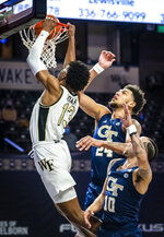 Wake Forest guard Quadry Adams (13) dunks a rebound as Georgia Tech forward Rodney Howard (24) looks on during an NCAA college basketball game Friday, March 5, 2021, in Winston-Salem, N.C. (Andrew Dye/The Winston-Salem Journal via AP)