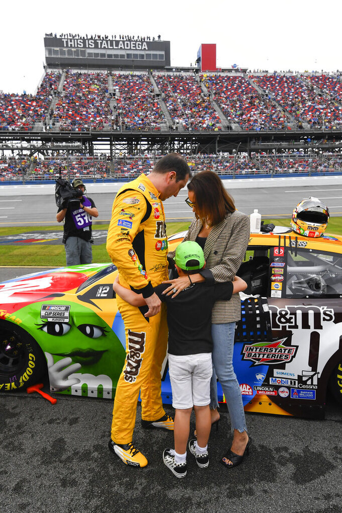 Kyle Busch, left, son Brexton, center, and wife Samantha put their arms around each other before a NASCAR Cup series auto race Sunday, Oct. 3, 2021, in Talladega, Ala. (AP Photo/John Amis)