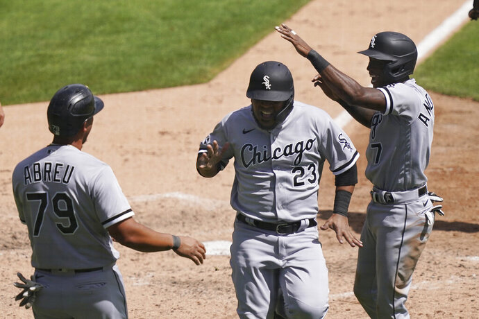 Chicago White Sox' Jose Abreu (79), Tim Anderson, right, and Edwin Encarnacion react after they all scored on teammate Luis Robert's double to right field during the fifth inning of a baseball game against the Detroit Tigers, Wednesday, Aug. 12, 2020, in Detroit. (AP Photo/Carlos Osorio)