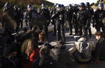 French police officers cordon off the access as pro-Catalan independence demonstrators try to block a major highway border pass near La Jonquera between Spain and France, Monday, Nov. 11, 2019. Protesters following a call to action by a secretive pro-Catalan independence group have closed off both sides of the AP7 highway at the major transportation hub of La Jonquera between France and Spain. (AP Photo/Felipe Dana)