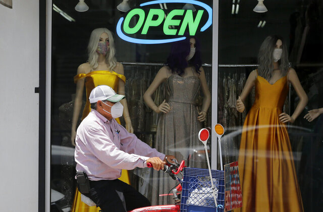 FILE - In this July 30, 2020, file photo, a cyclist passes a display window with mask covered mannequins at a dress store in McAllen, Texas. The number of laid-off workers applying for unemployment aid fell below 1 million last week for the first time since the pandemic intensified five months ago, yet still remains at a high level. (AP Photo/Eric Gay, File)