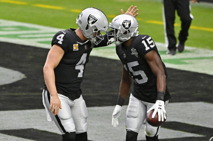 Las Vegas Raiders quarterback Derek Carr (4) celebrates after wide receiver Nelson Agholor (15) scored a touchdown against the Tampa Bay Buccaneers during the first half of an NFL football game, Sunday, Oct. 25, 2020, in Las Vegas. (AP Photo/David Becker)