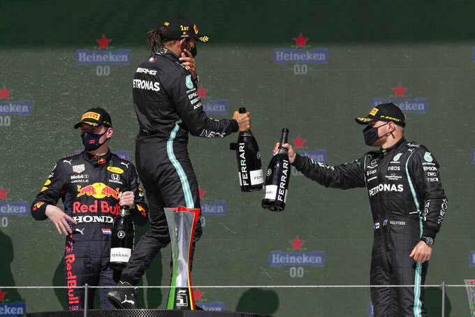 Winner Mercedes driver Lewis Hamilton of Britain celebrates with third placed Mercedes driver Valtteri Bottas of Finland, right, while second placed Red Bull driver Max Verstappen of the Netherlands, left, stands on the background on the podium of the Portugal Formula One Grand Prix at the Algarve International Circuit near Portimao, Portugal, Sunday, May 2, 2021. (AP Photo/Manu Fernandez)