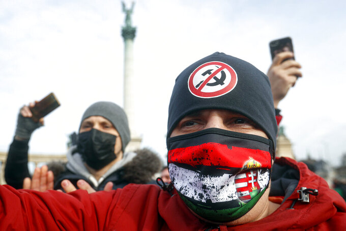 Hospitality sector workers take part in a protest, in Budapest, Hungary, Sunday, Jan. 31, 2021. Protesters gathered at a central square in Hungary's capital of Budapest on Sunday demanding a rethinking of the country's lockdown restrictions. As the lockdown limiting restaurants to take-away service approaches the three-month mark, many business owners complain that they have received little to none of the government's promised financial assistance while other businesses like shopping malls and retail stores have been permitted to remain open. (AP Photo/Laszlo Balogh)