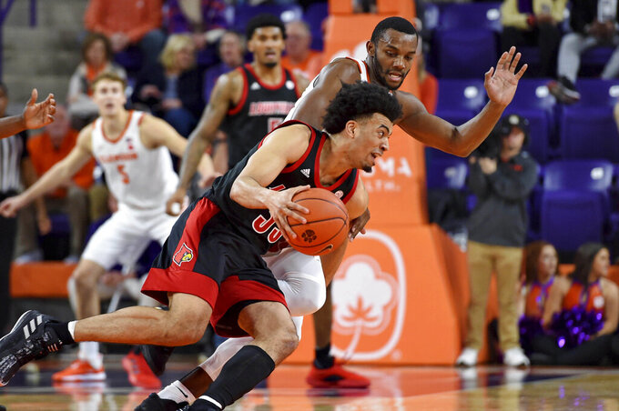 Louisville's Jordan Nwora, front, drives against Clemson's Aamir Simms during the first half of an NCAA college basketball game Saturday, Feb. 15, 2020, in Clemson, S.C. (AP Photo/Richard Shiro)