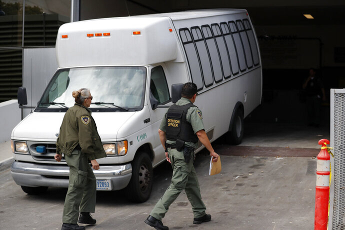 FILE - In this Tuesday, March 19, 2019 file photo, a van carrying asylum seekers from the border is escorted by security personnel as it arrives to immigration court, in San Diego. Scheduling glitches led an immigration judge to deny the Trump administration's request to order four Central American migrants deported because they failed to show for initial hearings Wednesday, March 20, 2019, dealing a setback to a highly touted initiative to make asylum seekers wait in Mexico while their cases wind through U.S. immigration courts. (AP Photo/Gregory Bull, File)
