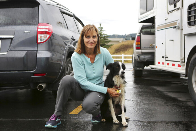 In this photo taken Tuesday, Sept. 17, 2019, is Carole King of Deer Park, Washington, holding her border collie, Katie, who went missing for 57 days before she was located in a Kalispell, Montana neighborhood. (Mackenzie Reiss/Daily Inter Lake via AP)