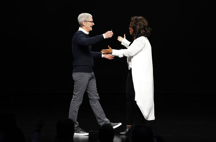Apple CEO Tim Cook and Oprah Winfrey prepare to embrace at the Steve Jobs Theater during an event to announce new products Monday, March 25, 2019, in Cupertino, Calif. (AP Photo/Tony Avelar)