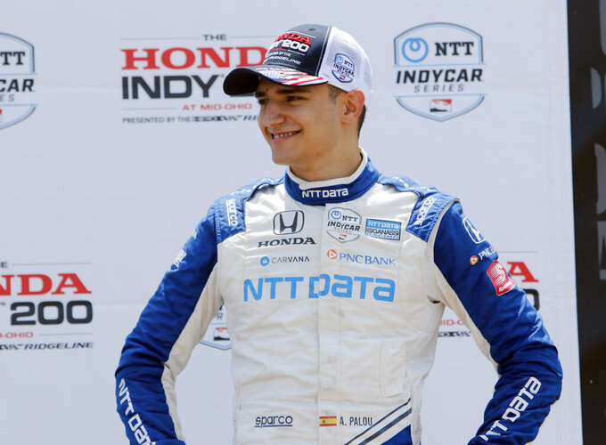 FILE - Alex Palou smiles in victory lane after placing third in an IndyCar race at Mid-Ohio Sports Car Course in Lexington, Ohio, in this Sunday, July 4, 2021, file photo.  When a pair of poor finishes cost Palou the IndyCar points lead, the second-year driver found teammate Jimmie Johnson for a pair of pep talks. Johnson may be an IndyCar rookie on the track, but the intangibles he brings to Chip Ganassi Racing as a seven-time NASCAR champion are invaluable.  (AP Photo/Tom E. Puskar, File)