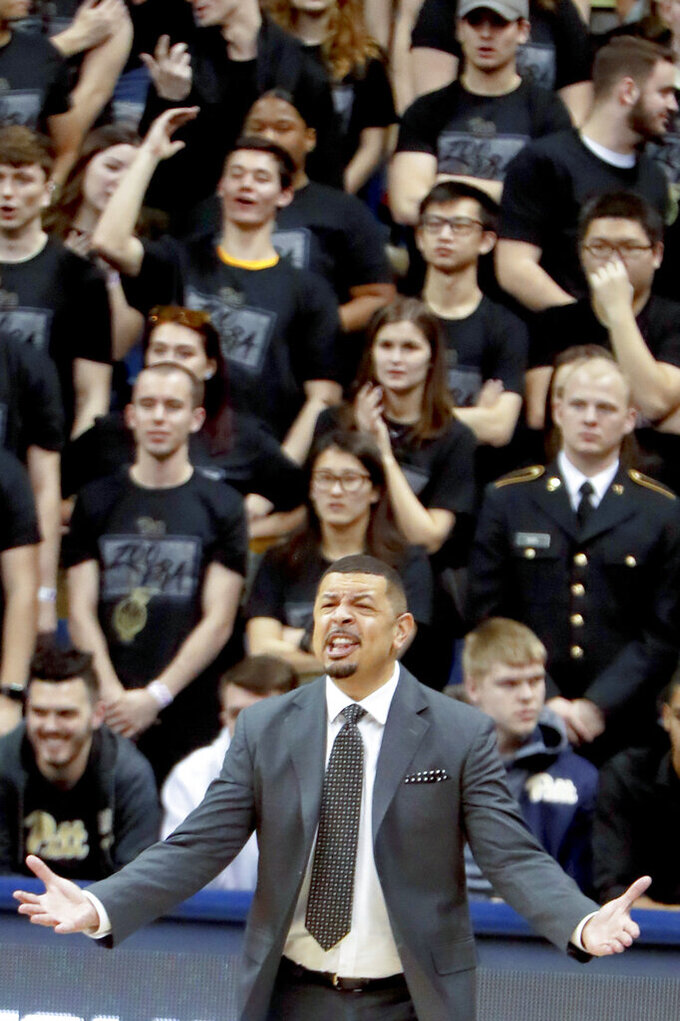 FILE—In tis file photo from Feb. 9, 2019, Pittsburgh basketball fans, all in black, stand behind head coach Jeff Capel as he coaches his team against North Carolina State in an NCAA college basketball game in Pittsburgh. Capel's first season at Pittsburgh brought optimism. Now comes the hard part: building off it while playing in arguably the nation's toughest conference. (AP Photo/Keith Srakocic, File)